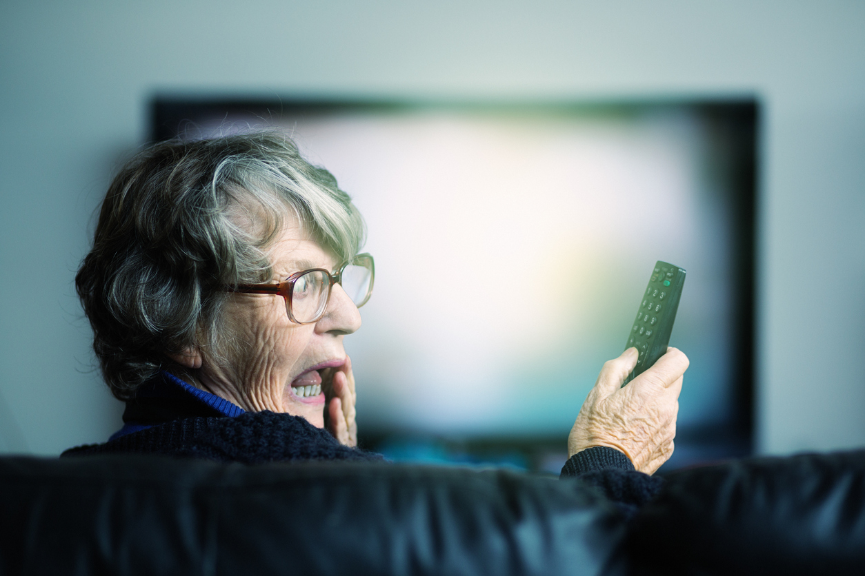 An older woman looks surprised at a television remote.
