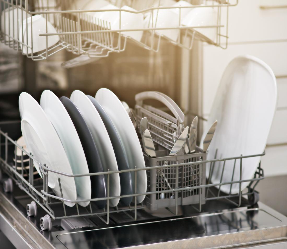 Stroj za pranje posuđa pun čistih bijelih posuđa.