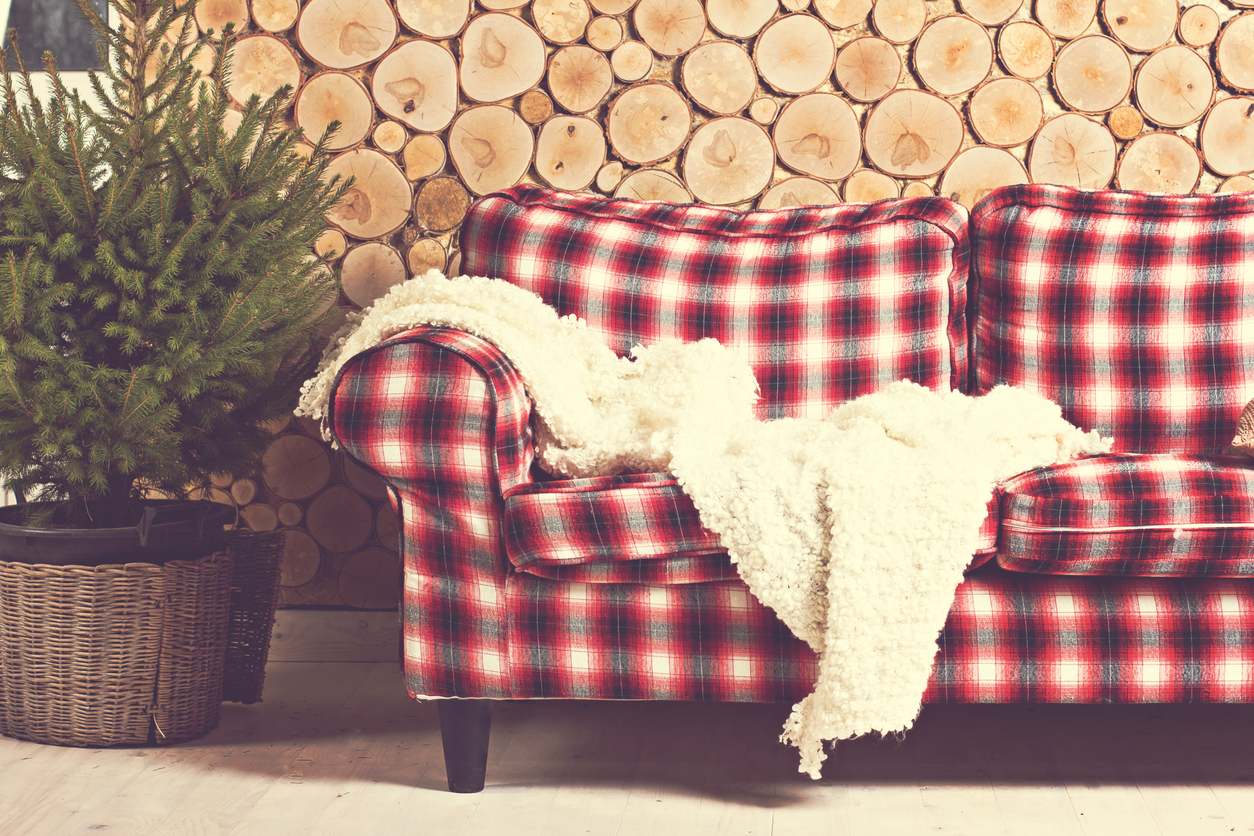 A Red Tartan Couch In Front Of Wall Made Wooden Log Cross Sections