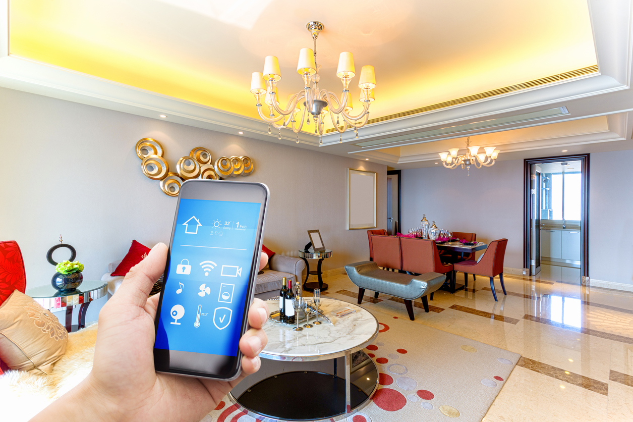A hand holds out a smart phone in the foreground of an ornate living room.