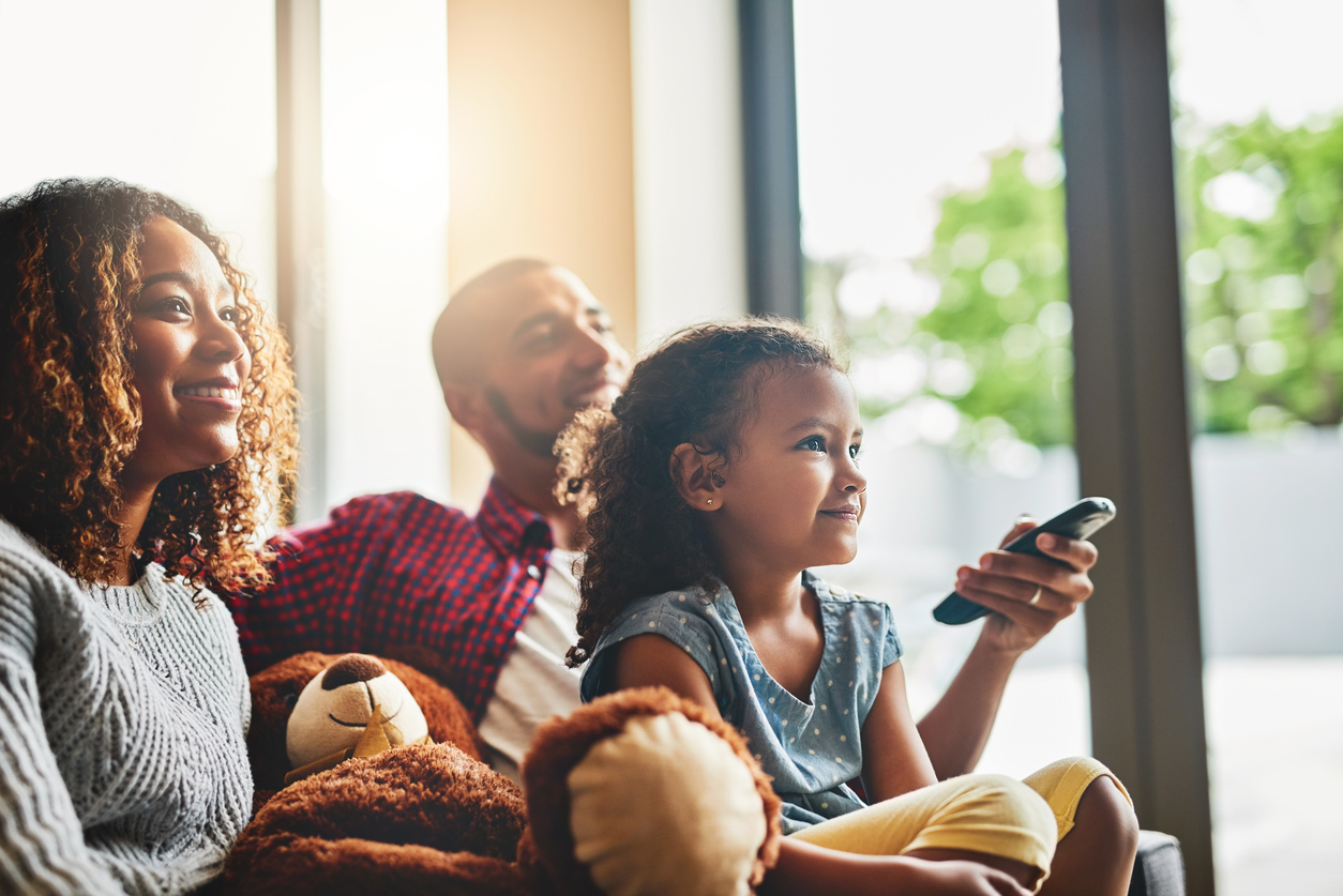 A mother, father, and young daughter sit together on the couch. The father holds a television remote.