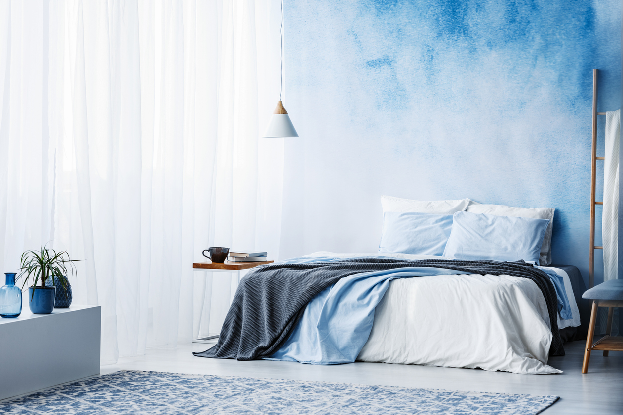 A Bedroom With Blue Walls Carpet And Comforter On Large